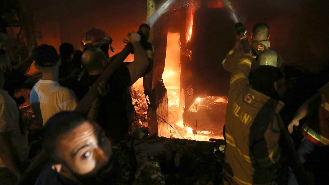 Firefighters and civilians gather at the site after a diesel tank exploded in the neighborhood of Tariq al-Jadideh, in Beirut, Oct. 9, 2020. (AP)