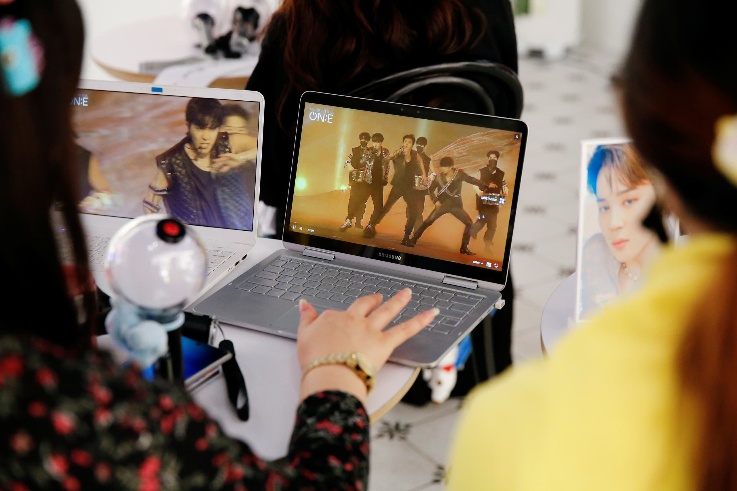 Fans of K-pop idol boy band BTS watch a live streaming online concert, wearing a protective masks to avoid the spread of the coronavirus disease (COVID-19), at a cafe in Seoul, South Korea October 10, 2020. REUTERS/Heo Ran