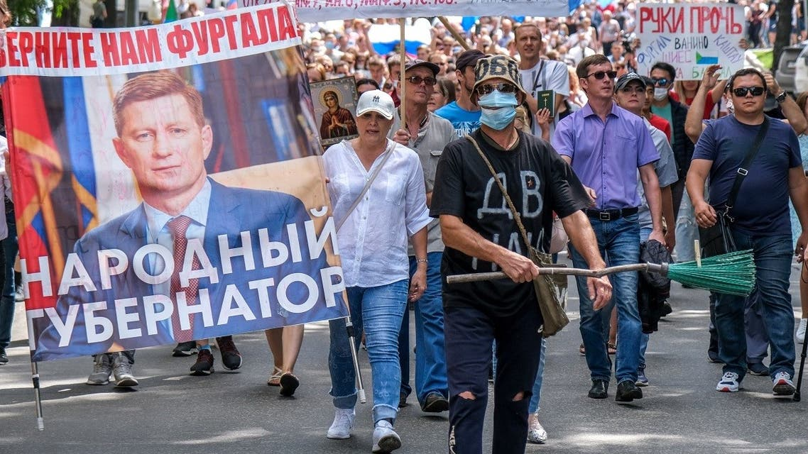 """People carry a banner reading """"Return Furgal for us"""", during an unauthorised rally in support of Sergei Furgal in the Russian far eastern city of Khabarovsk on August 8, 2020. (AFP)"""
