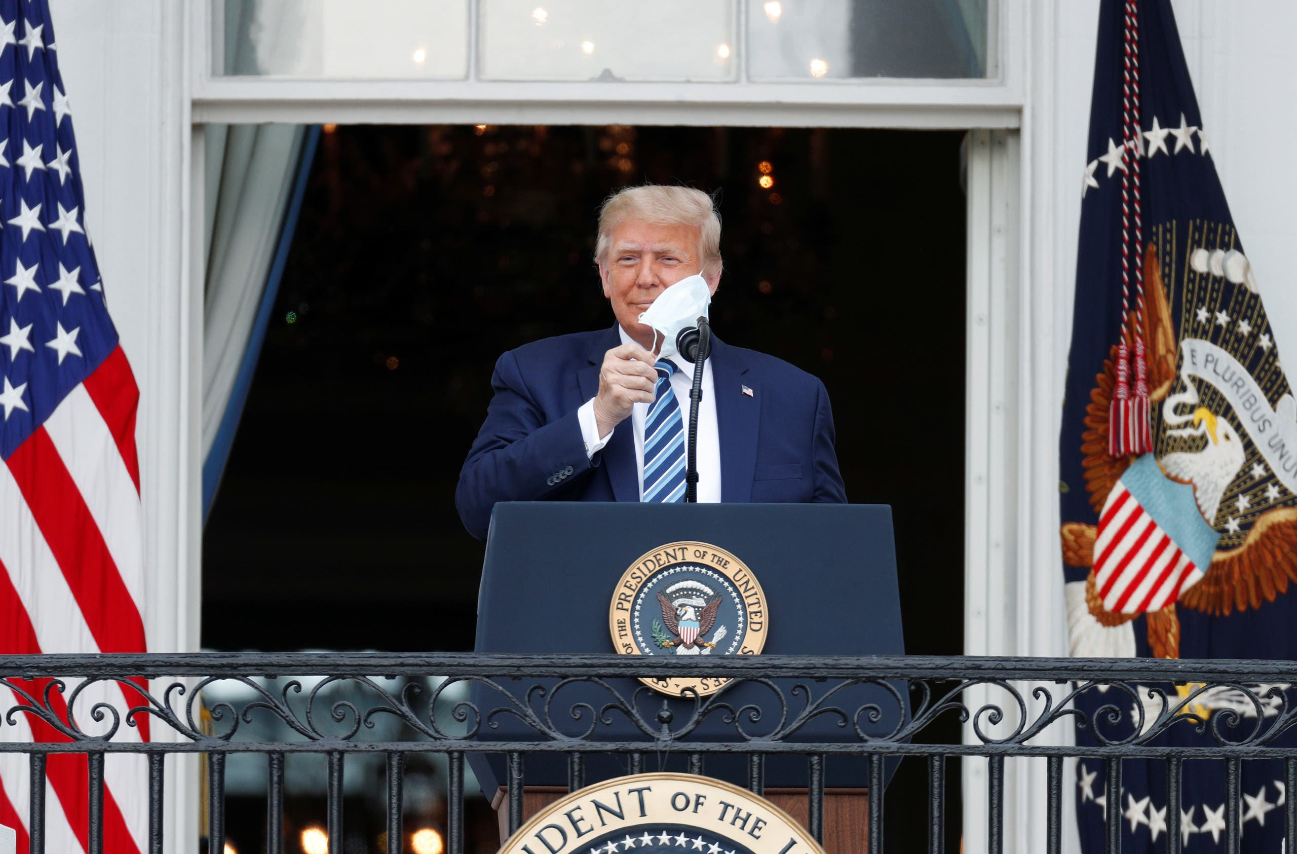 President Trump takes off his face mask as he comes out on a White House balcony to speak to supporters gathered on the South Lawn for a campaign rally in Washington, US, October 10, 2020. (Reuters)