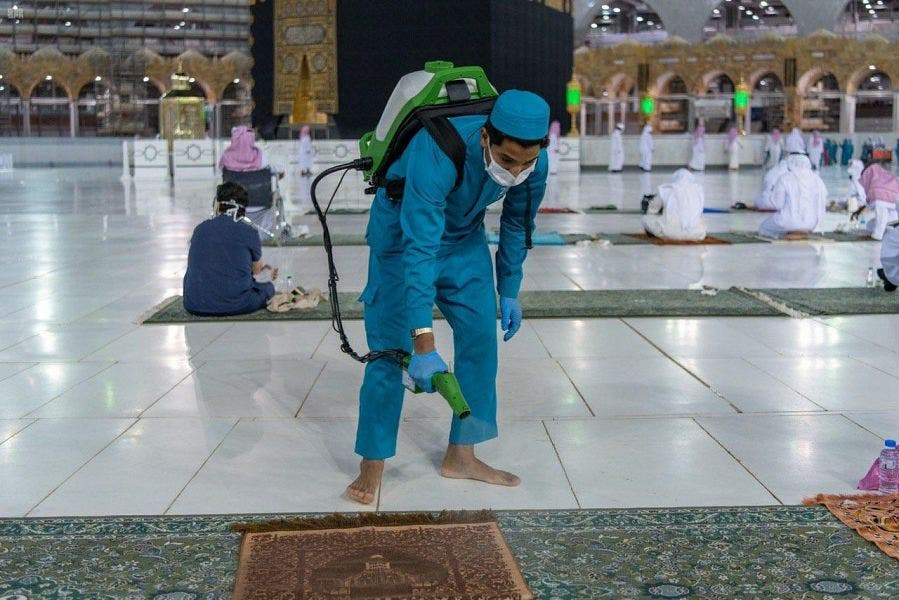 A worker sterilizes the grounds around the holy Kaaba. (Supplied)