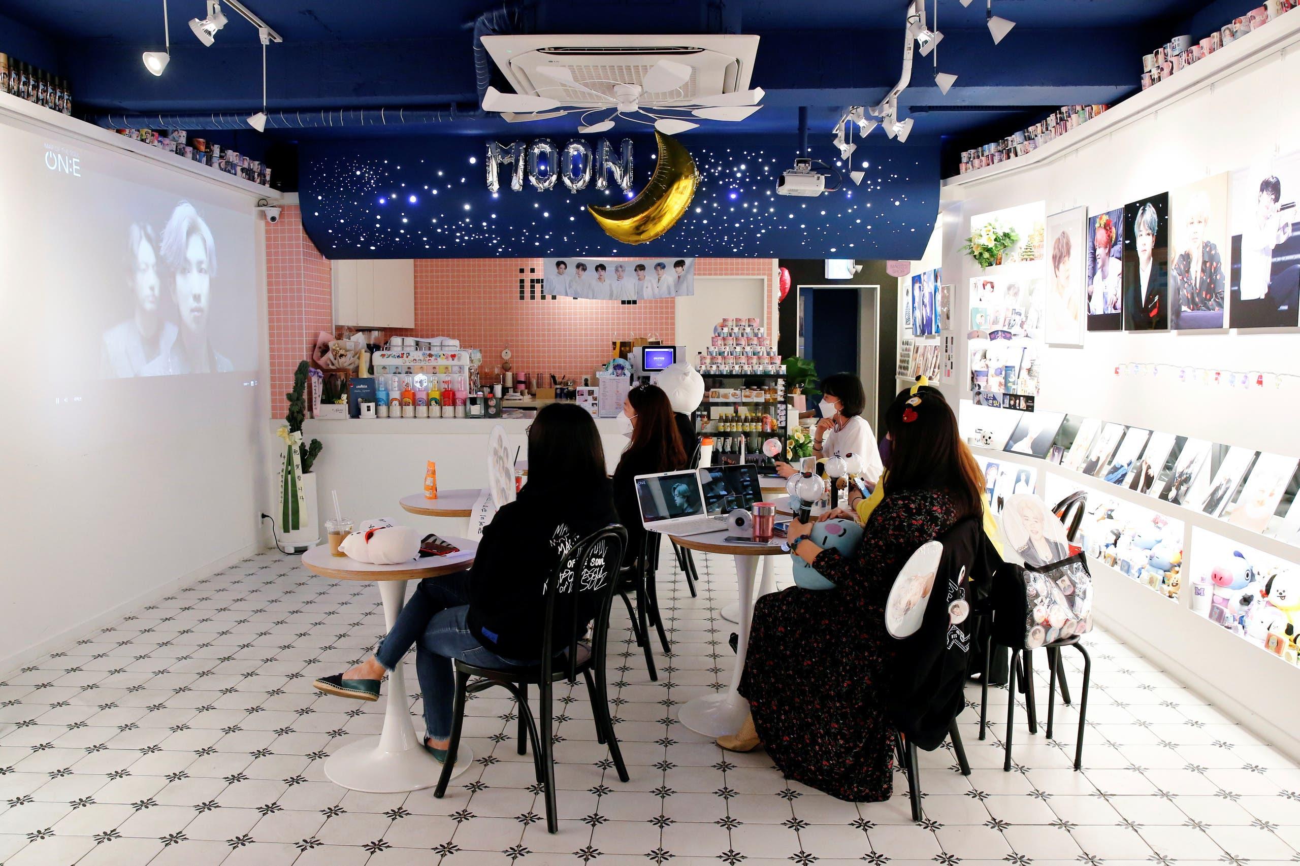 """عشاق لفرقة """"بي. تي. اس"""" يشاهدون الحفل على شاشة كبيرة في مقهى في سيول"""