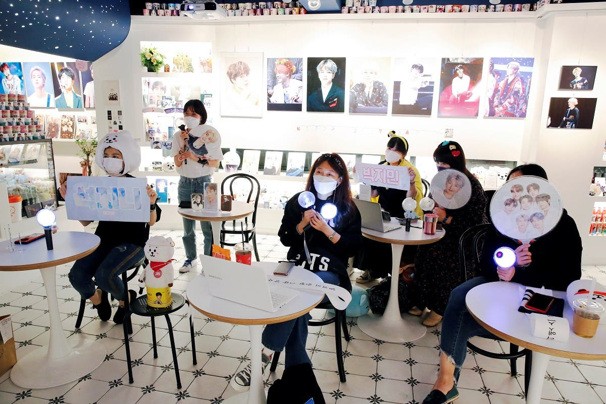 Fans of K-pop idol boy band BTS watch a live streaming online concert, wearing a protective masks at a cafe, in Seoul. (Reuters)