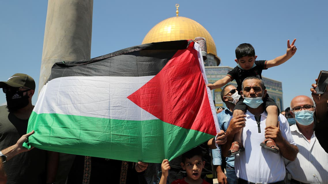 People hold a Palestinian flag during a protest against the United Arab Emirates, in Jerusalem's Old City, August 14, 2020. (Reuters)