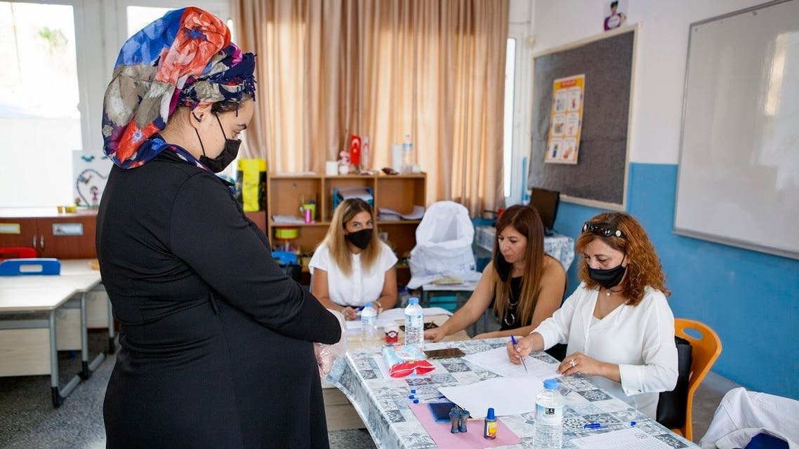 A Turkish-Cypriot woman prepares to vote at a polling station in the northern part of Nicosia, the capital of the self-proclaimed Turkish Republic of Northern Cyprus (TRNC), during the presidential election on October 11, 2020. (AFP)