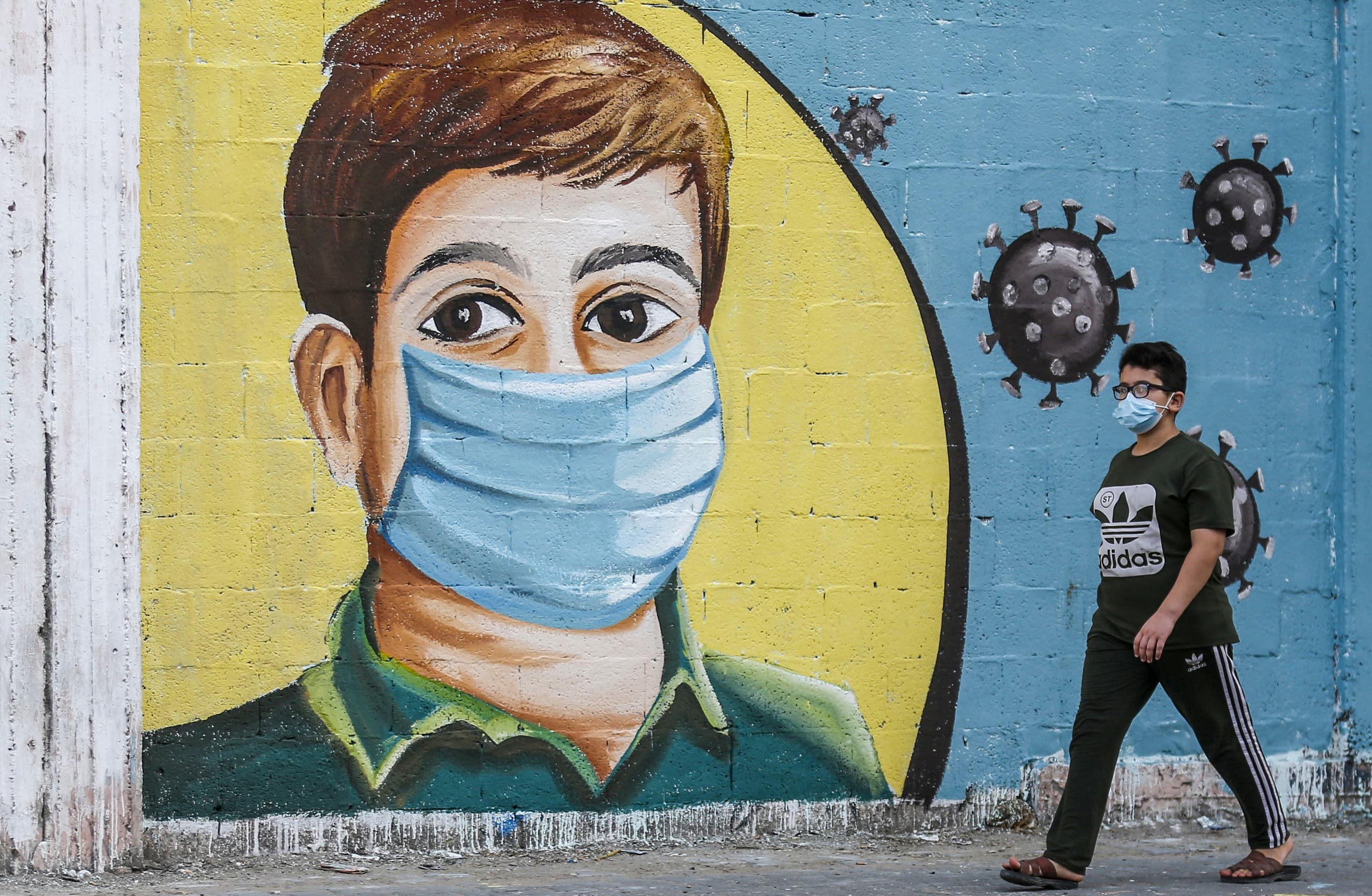 A Palestinian boy walks past a coronavirus awareness mural in Rafah in the southern Gaza Strip on September 14, 2020. (AFP)