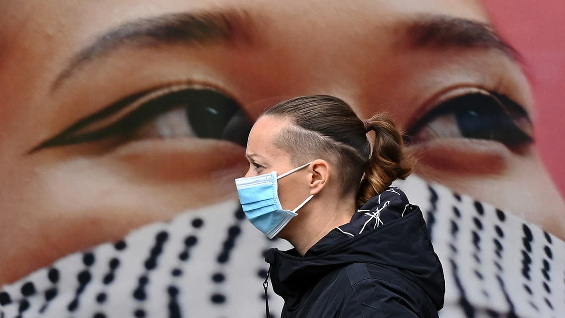 A pedestrian wearing a face mask as a precaution against the transmission of the novel coronavirus, walks past a poster of a person wearing a face covering, in the high street in west London on October 11, 2020. (AFP)