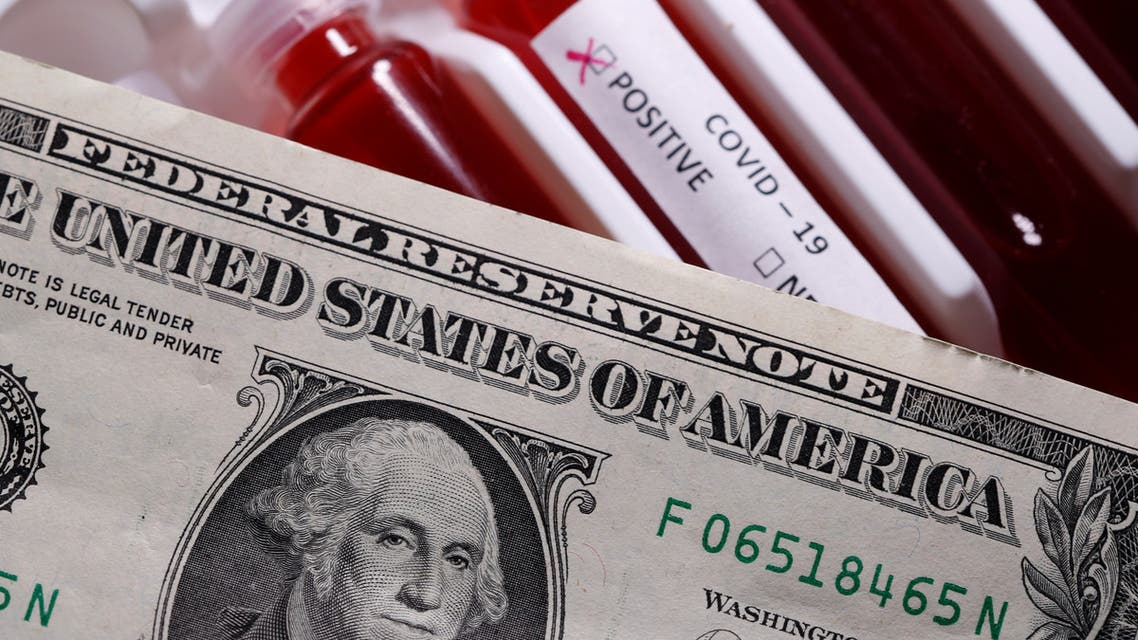 A dollar banknote is placed on the test tubes with fake blood labelled with the coronavirus disease (COVID-19) in this illustration taken, March 27, 2020. (Reuters)