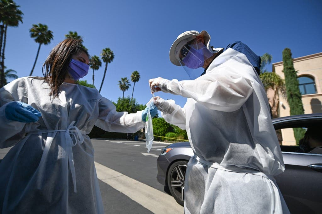 Healthcare workers collect a test sample at a drive-through coronaviurs testing center on September 29, 2020 in Los Angeles, California. (AFP)
