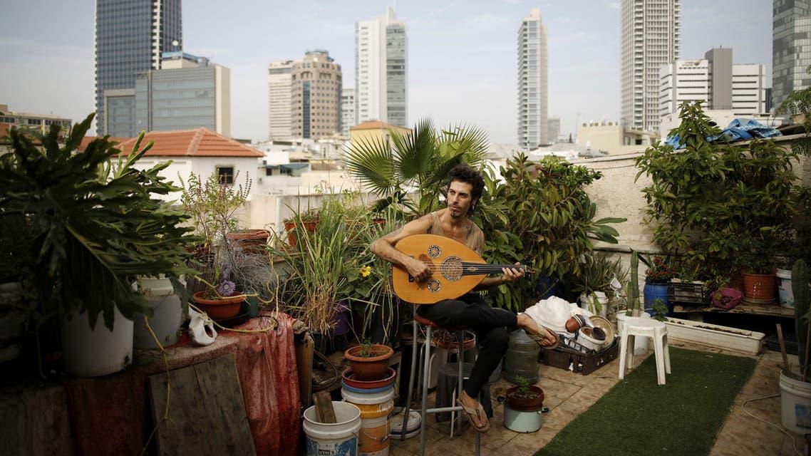Musician Iyar Semel plays an oud on his rooftop garden in Tel Aviv, Israel, November 13, 2017. (File photo: AP)