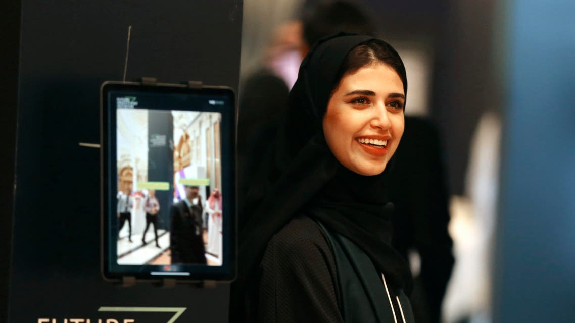 A Saudi organizer at the Future Investment Initiative conference, FII, smiles as she welcomes participants, in Riyadh, Saudi Arabia on Oct. 29, 2019. (AP)
