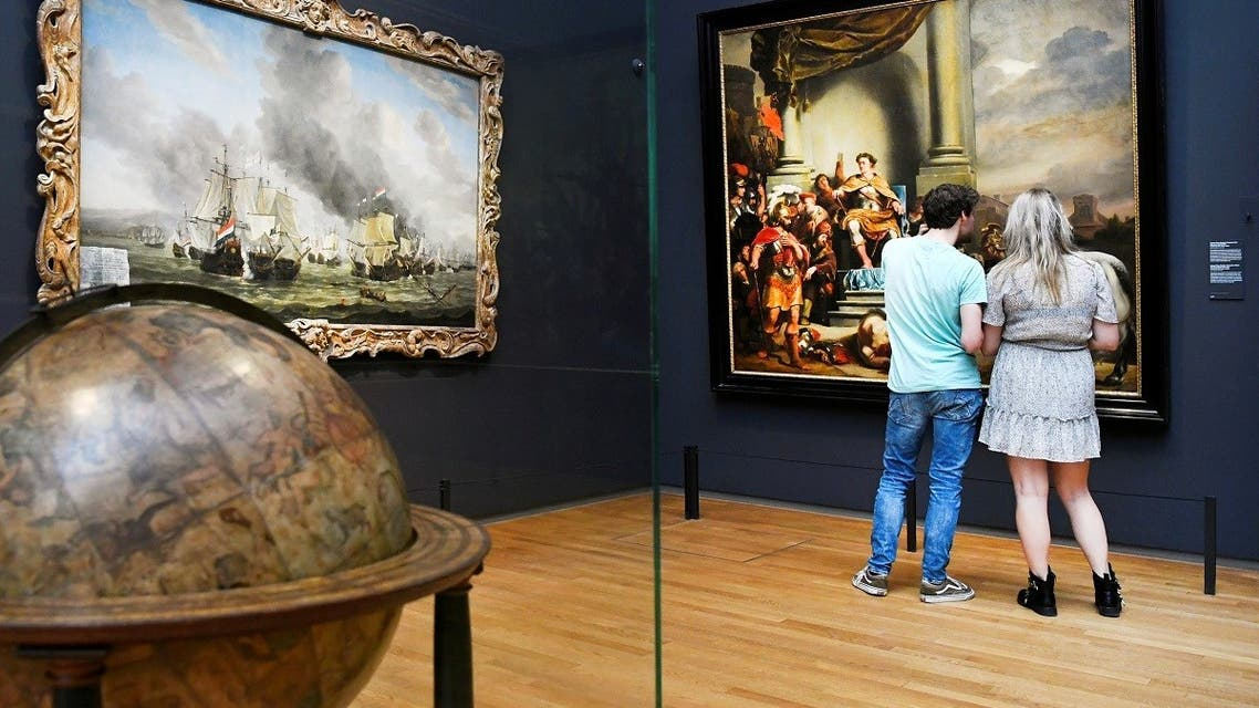 People look at a painting at the Rijksmuseum that reopened as Netherlands eases some of the lockdown measures put in place during the coronavirus outbreak, in Amsterdam, Netherlands. (Reuters)