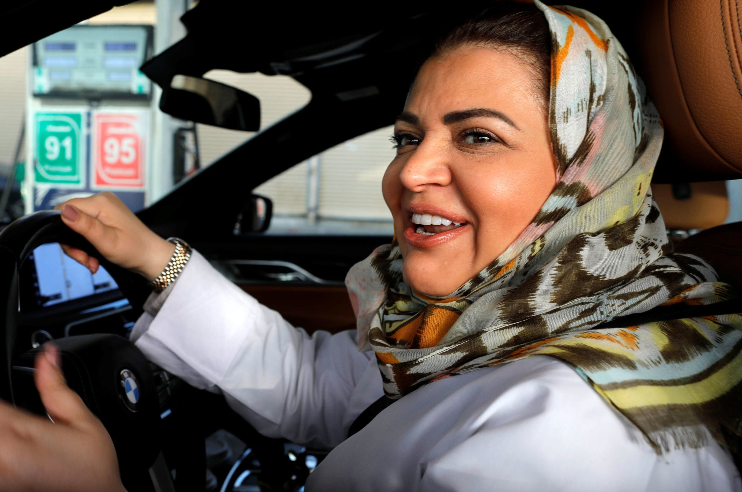 Samira al-Ghamdi, a practicing psychologist, smiles while making a stop to refuel her car as she drives to work in Jeddah, Saudi Arabia June 24, 2018. (Reuters)