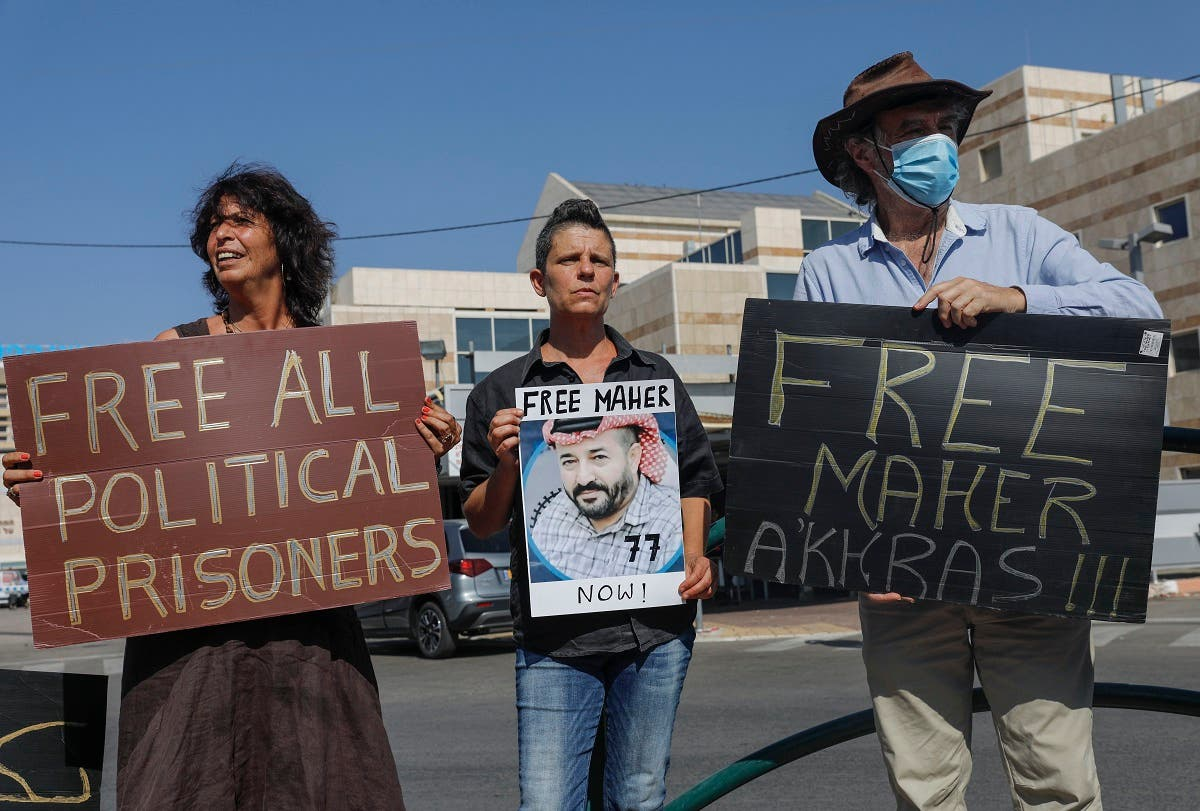 Israeli left-wing activists lift placards during a demonstration calling for the release of Palestinian administrative detainees, including Maher al-Akhras in front of Kaplan medical center in the central city of Rehovot, October 11, 2020. (Ahmad Gharabli/AFP)