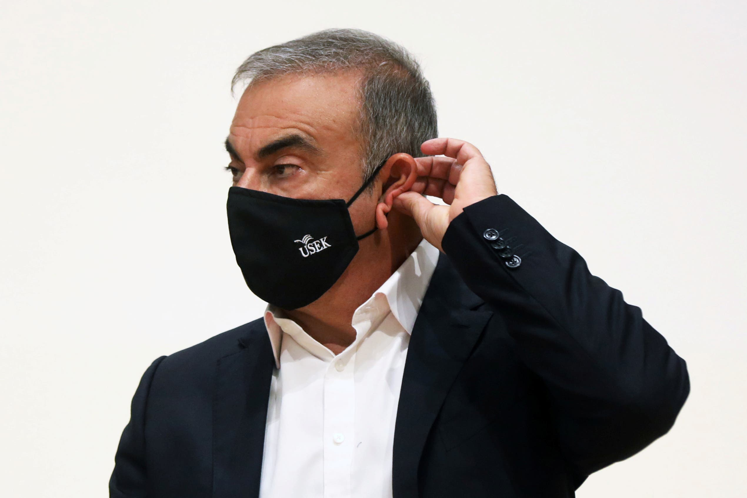 Carlos Ghosn, the former Nissan and Renault chief executive, adjusts his protective face mask during a news conference at the Holy Spirit University of Kaslik, in Jounieh, Lebanon September 29, 2020. (Reuters)
