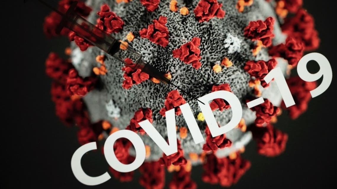 This photograph taken on October 7, 2020 shows a syringe on an illustration representing coronavirus, in Toulouse, southwestern France. (AFP)
