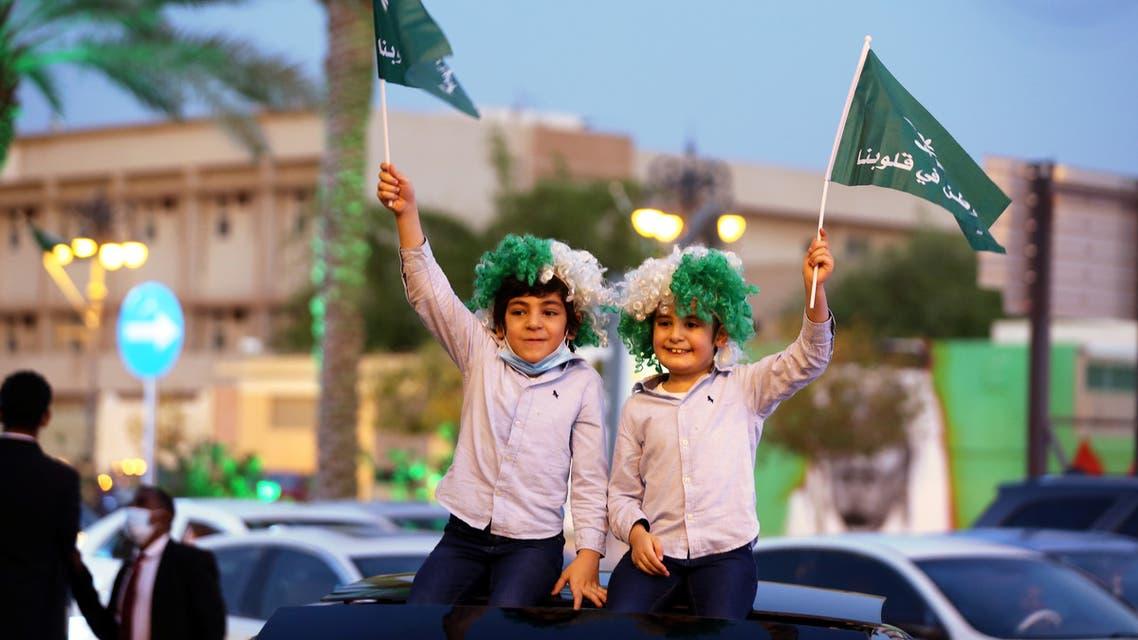 Children wave flags as people celebrate Saudi Arabia's 90th annual National Day, amid the spread of the coronavirus disease (COVID-19) in Riyadh, Saudi Arabia September 23, 2020. (Reuters)