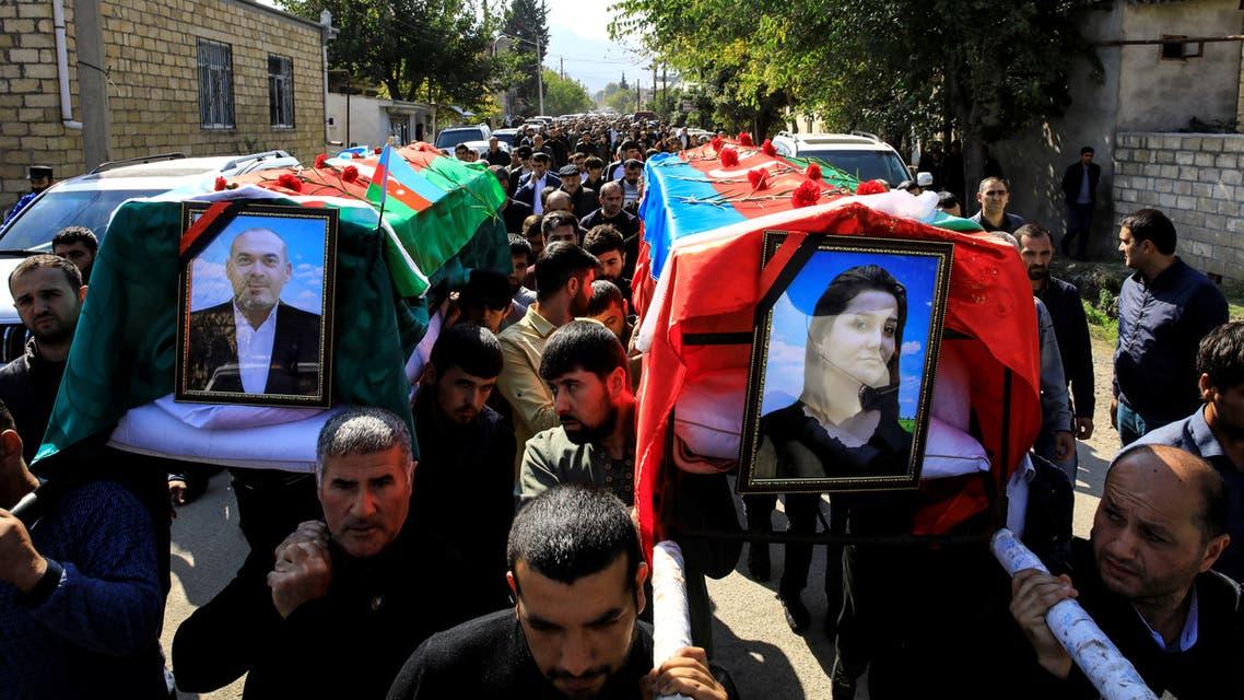 People carry the coffins of Anar Aliyev and his wife Nurcin Aliyeva, killed in Ganja attack during the fighting over the breakaway region of Nagorno-Karabakh, in the city of Shamkir, Azerbaijan October 12, 2020. REUTERS/Umit Bektas