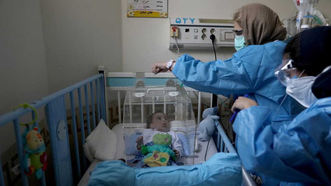 A mother wearing a protective suit and mask tends to her baby who is affected by the coronavirus disease (COVID-19), at Hazrate Ali Asghar Hospital, in Tehran, Iran September 27, 2020. Picture taken September 27, 2020. Majid Asgaripour/WANA (West Asia News Agency) via REUTERS ATTENTION EDITORS - THIS IMAGE HAS BEEN SUPPLIED BY A THIRD PARTY.