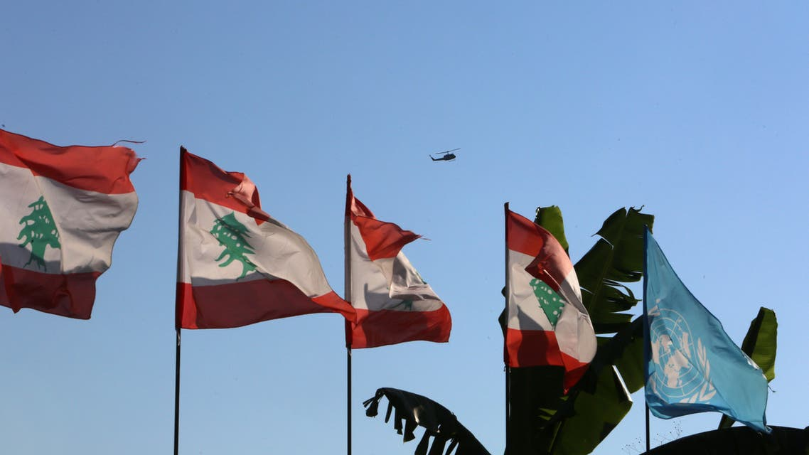 Lebanese and UN flags flutter as an aircraft flies in Naqoura ahead of talks between Israel and Lebanon on disputed waters, near the Lebanese-Israeli border. (Reuters)