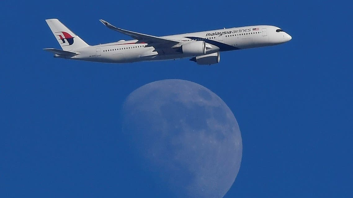 A Malaysian Airlines Airbus A350-900 passenger aircraft is seen flying in front of the moon, over London, Britain. (Reuters)_155477375_RC1638411200_RTRMADP_3_BRITAIN-WEATHER