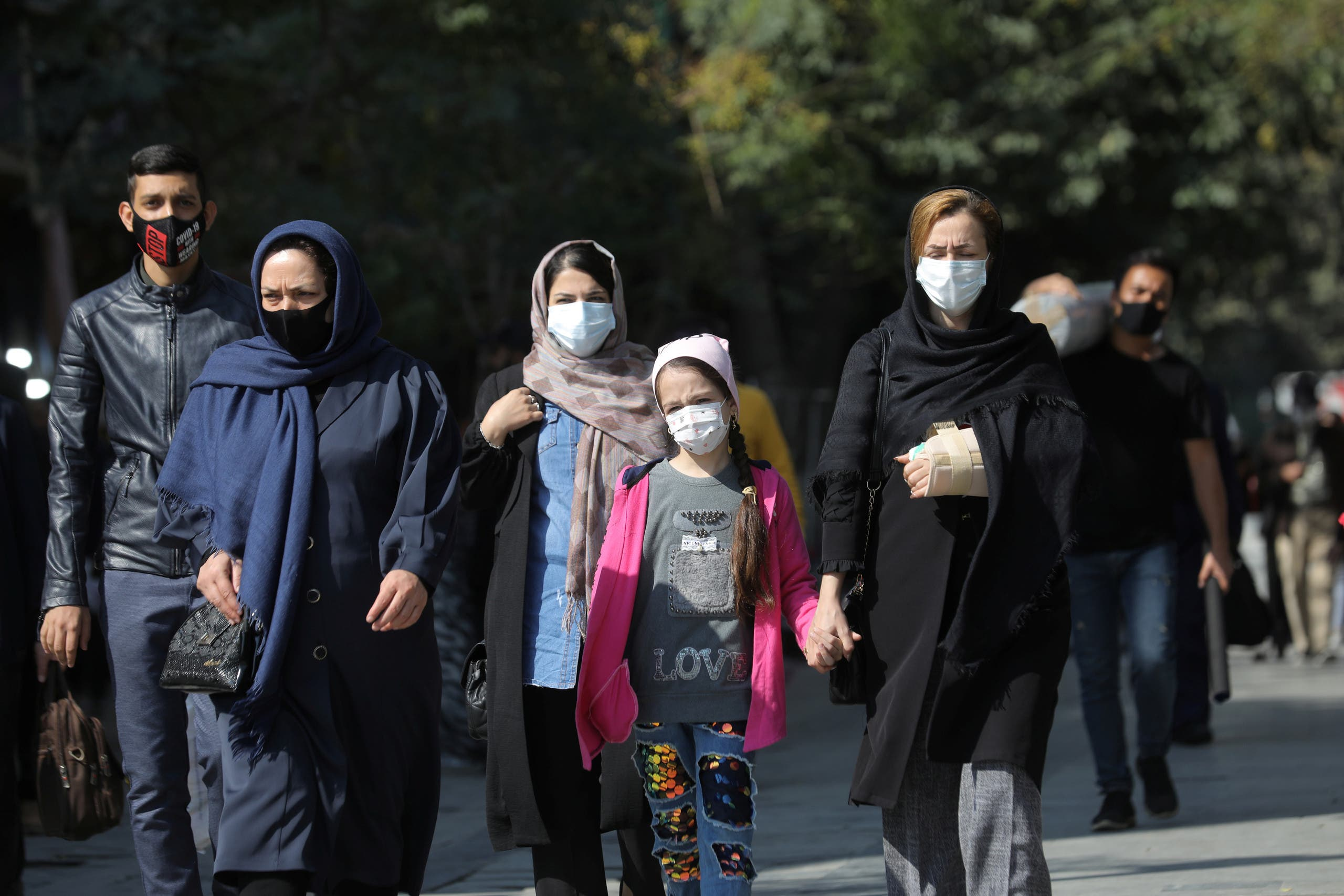 Iranians wearing face masks walk on a street after Iranian authorities made it mandatory for all to wear face masks in public following the outbreak of the coronavirus disease (COVID19), in Tehran Iran October 10, 2020. (Reuters)