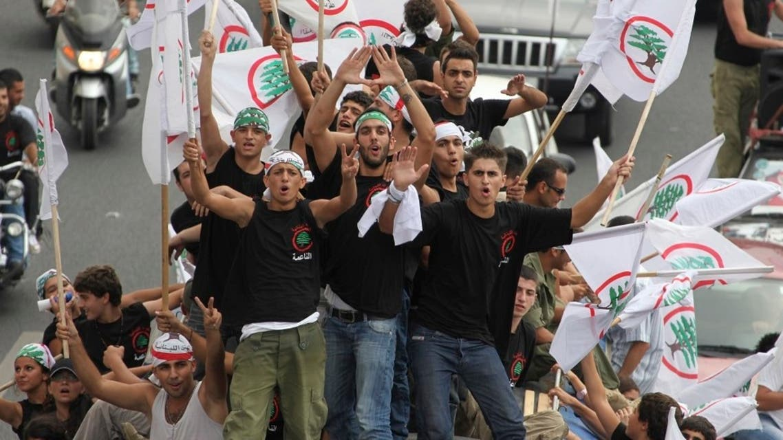 Supporters of the Lebanese Forces carry flags and shout slogans atop a bus on their way to attend a commemoration mass, Sept. 25, 2010. (Reuters)