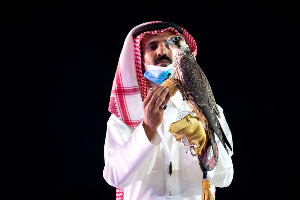 A Saudi man displays the falcon during the auction in King Abdulaziz Festival in Mulham, north of Riyadh, Saudi Arabia, October 13, 2020. (Media Center Saudi Falcons Club Auction via Reuters)