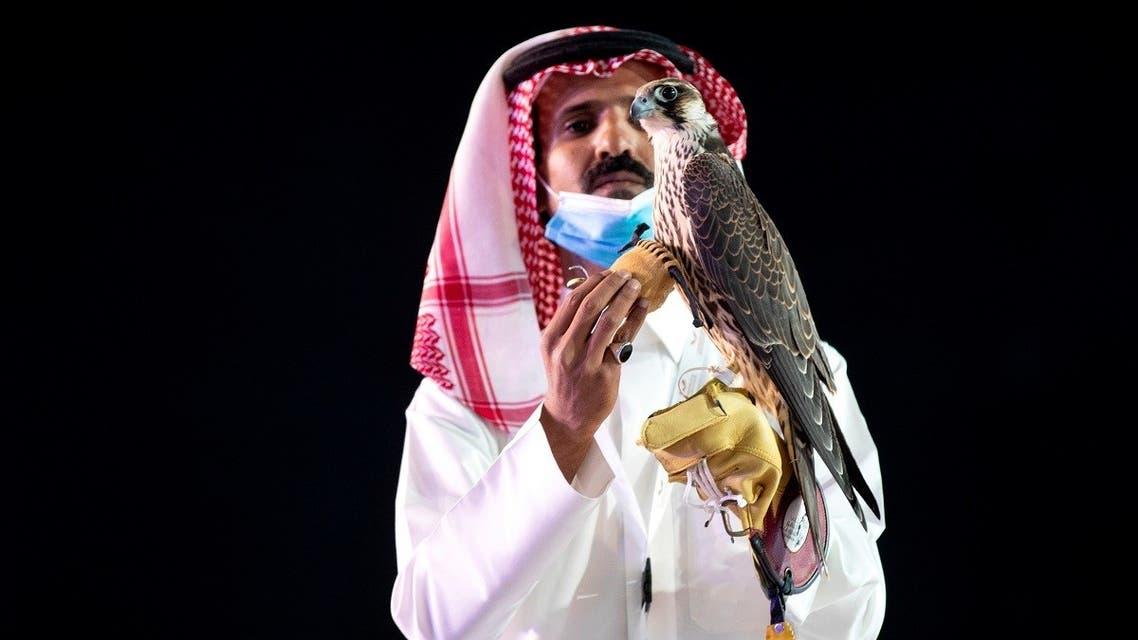 A Saudi man displays the falcon during the auction at Saudi Falcons Club Auction in King Abdulaziz Festival in Mulham, north of Riyadh, Saudi Arabia, October 13, 2020. (Media Center Saudi Falcons Club Auction via Reuters)