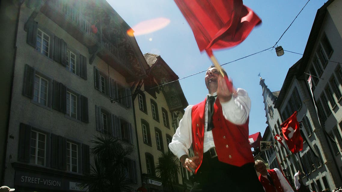 A man waves a Swiss flag at the 26th federal yodelling festival in Aarau, Switzerland, June 19, 2005. 200,000 people attended this weekend's national yodelling festival which is held every three years. (File photo: Reuters)