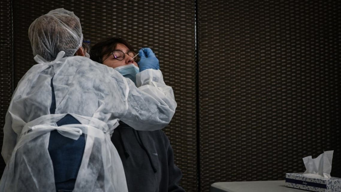 A health worker collects a swab sample to test for the Covid-19 disease caused by the coronavirus in Lyon's sports arena which was turned into a giant screening centre, on October 12, 2020. (AFP)