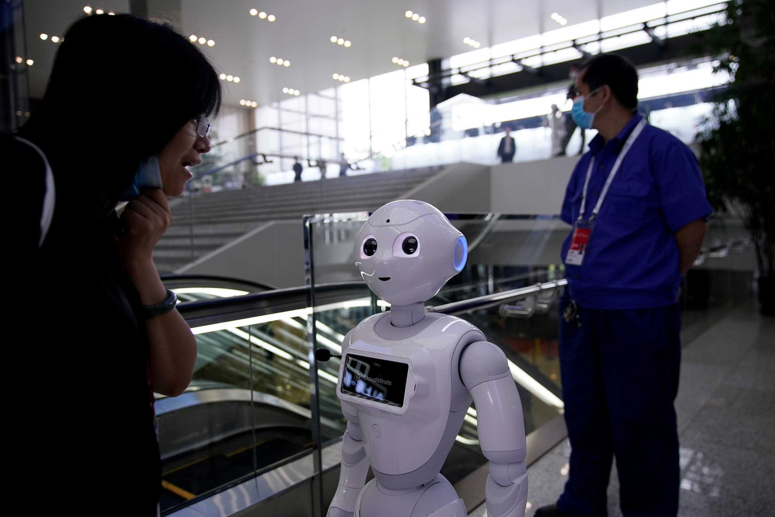 People wearing face masks following the coronavirus disease (COVID-19) outbreak are seen near a robot at the venue for the World Artificial Intelligence Conference (WAIC) in Shanghai, China July 9, 2020. (Reuters)