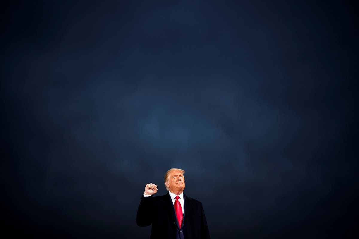 US President Donald Trump makes a fist during a campaign rally at Des Moines International Airport in Des Moines, Iowa. (Reuters)