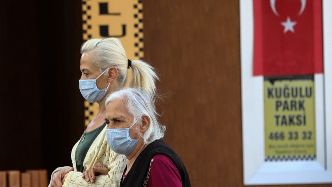 Two women wearing protective face masks against the spread of the novel coronavirus, Covid-19, walk together in Ankara on October 12, 2020. (AFP)