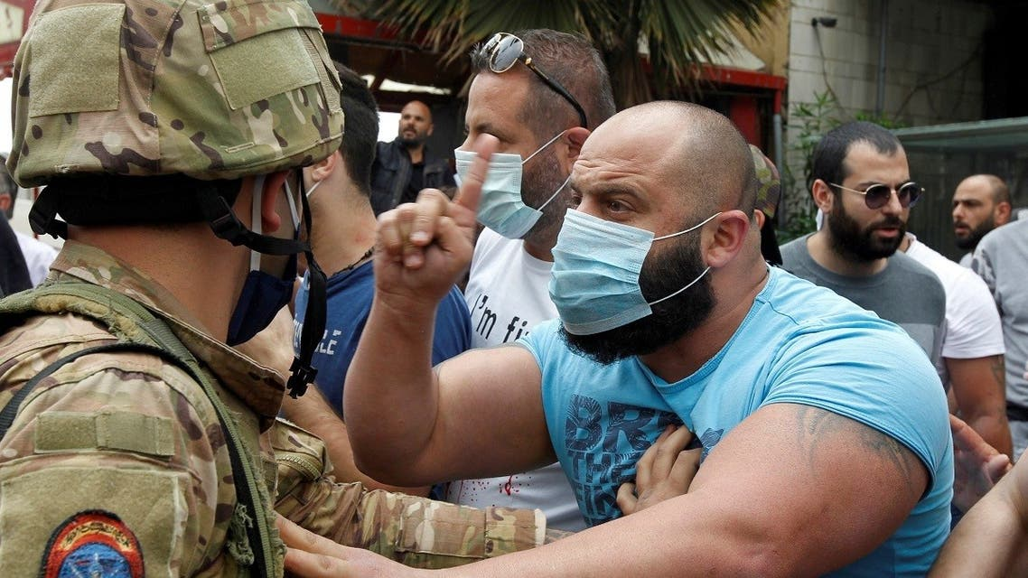 A Lebanese demonstrator gestures to a Lebanese soldier, during a protest against the collapsing Lebanese pound currency and the price hikes, in Lebanon, April 27, 2020. (Reuters)