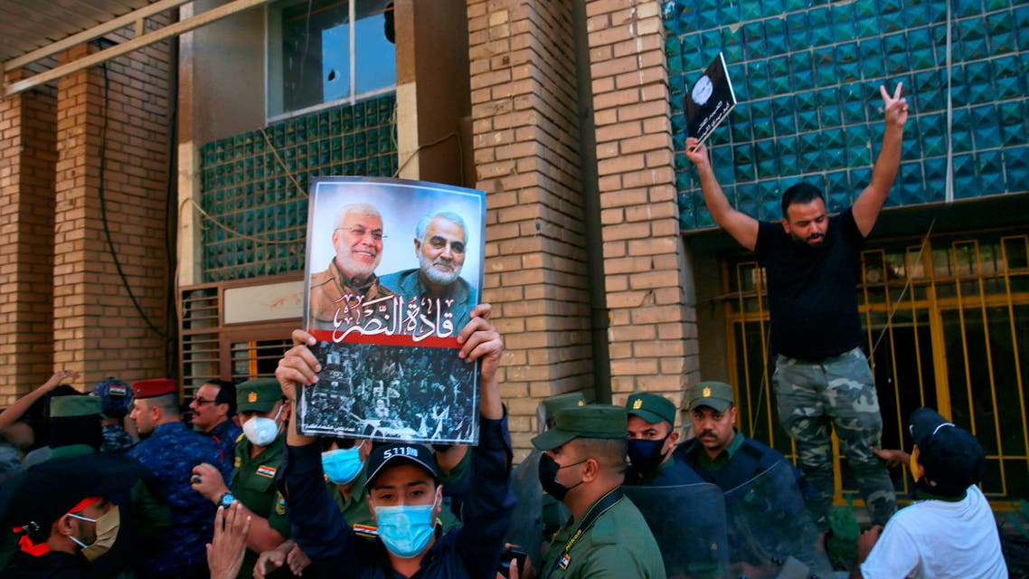 A supporter of an Iran-backed militia holds a poster of Iranian General Qassem Soleimani, deputy commander Abu Mahdi al-Muhandis during a protest by pro-Iranian militiamen and their supporters in Baghdad on Oct. 17, 2020. (AP)