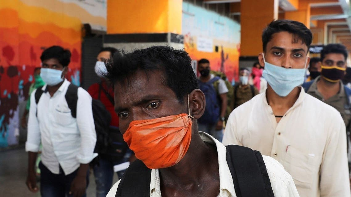 Passengers wearing face masks stand in line to get tested for coronavirus, at a railway station, in New Delhi, India, Oct. 5, 2020. (Reuters)