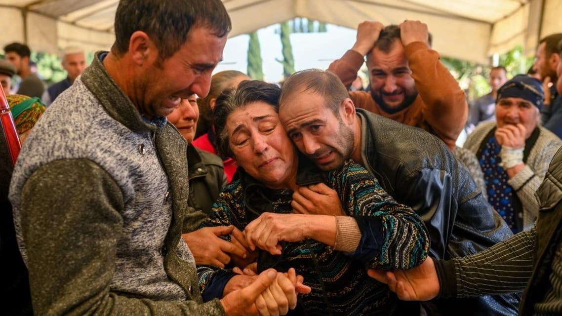 Relatives of a family killed when a rocket hit their home, mourn during their funeral in the city of Ganja, Azerbaijan, on October 17, 2020 during fighting over the breakaway region of Nagorno-Karabakh. (AFP)