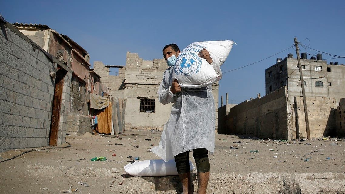 Palestinian refugees receive aid distributed by UNRWA amid the Covid-19 coronavirus disease outbreak, at the United Nations center in Gaza City, Oct. 8, 2020. (AFP)