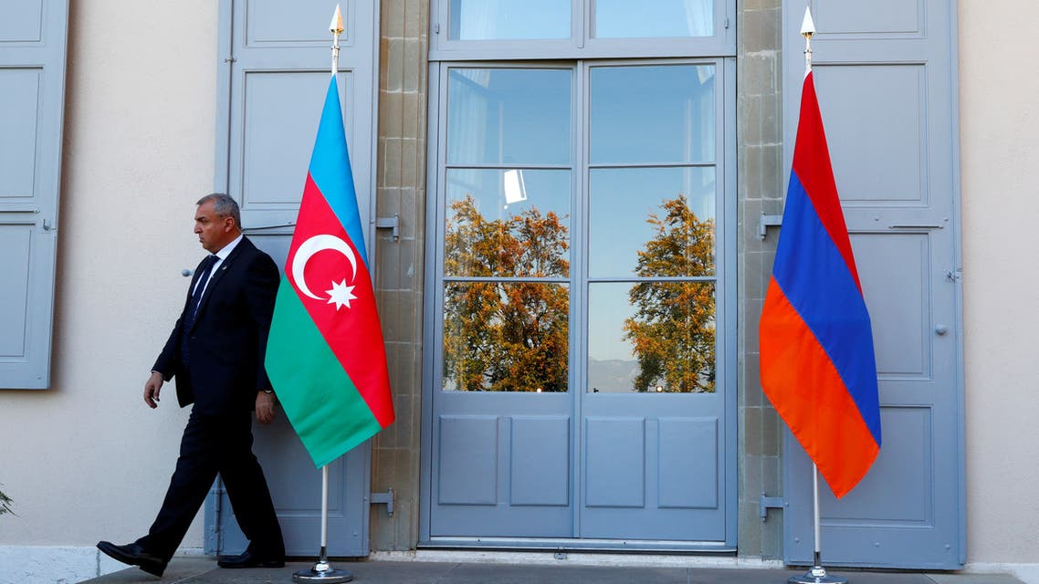 A security guard walks past an Azerbaijan (L) and Armenian flag at the opening of talks in Geneva, Switzerland October 16, 2017. (File photo: Reuters)