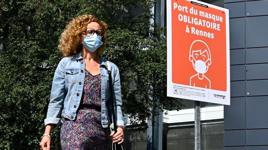 A woman wearing a face mask walks past a sign reading Wearing a mask is mandatory in Rennes in a street of Rennes, western France on September 12, 2020. (AFP)