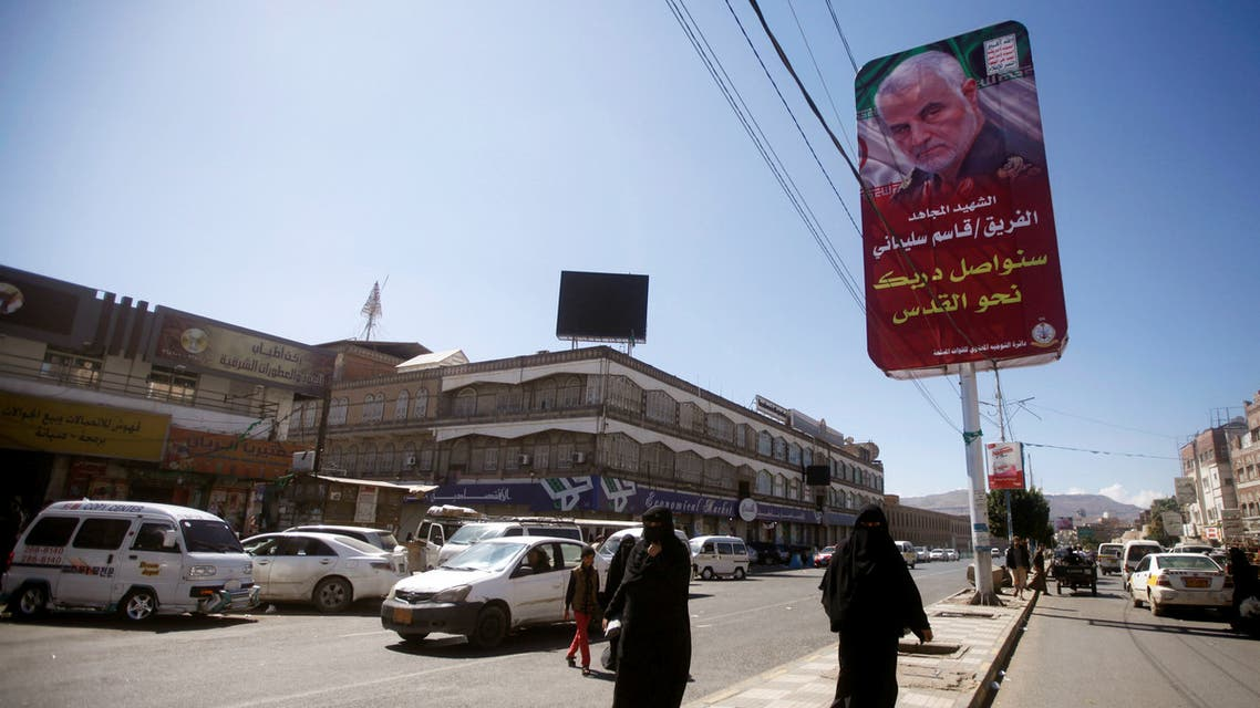 Women pass next to a billboard with posters of Iranian Major-General Qassem Soleimani, head of the elite Quds Force, who was killed in an air strike at Baghdad airport, in Sanaa, Yemen January 9, 2020. Picture taken January 9, 2020. REUTERS/Mohamed al-Sayaghi