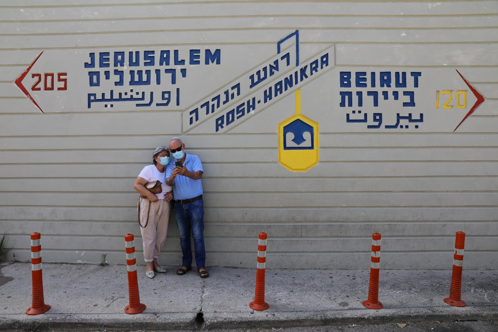A couple wearing face masks, visit the Rosh Hanikra border crossing with Lebanon, in Rosh Hanikra, northern Israel October 13, 2020. (Reuters)