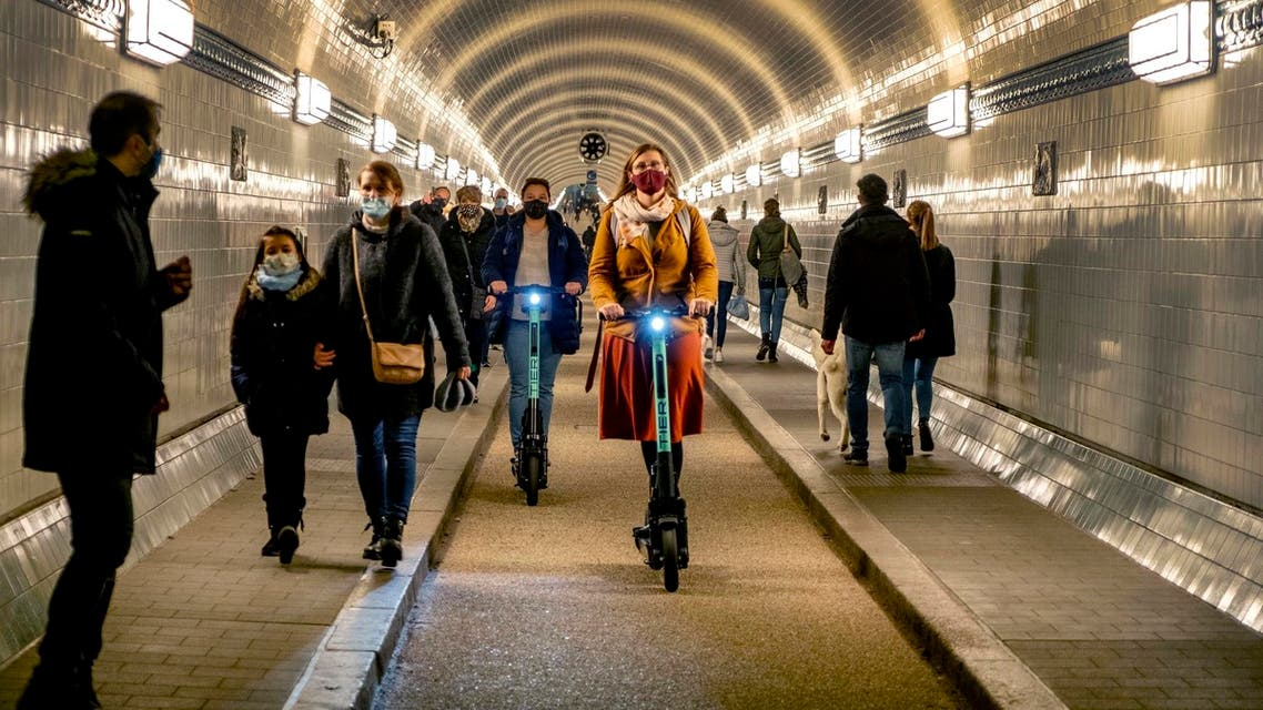 People wear face masks as they ride an E-scooter in the Old Elbe Tunnel in Hamburg, Germany, Thursday, Oct. 15, 2020. To avoid the spread of the coronavirus the use of a face mask in the 117-year-old tunnel under the Elbe river is mandatory. (AP Photo/Michael Probst)