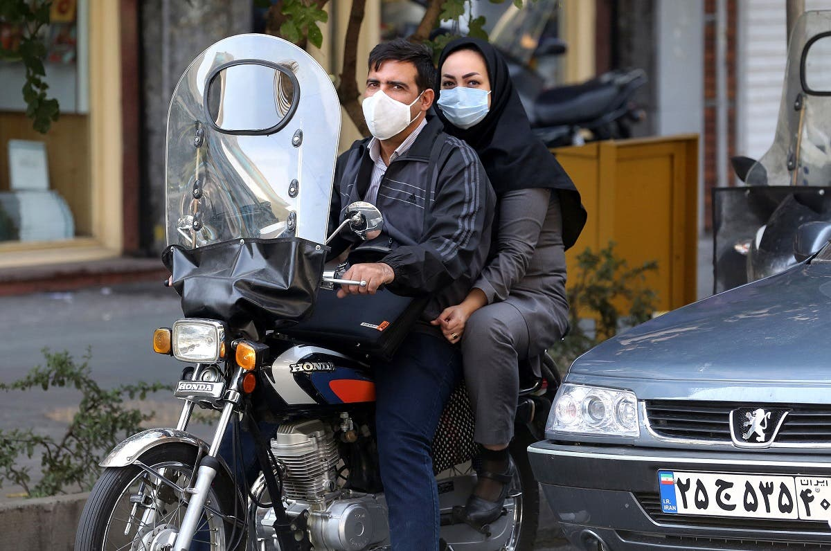 Iranians wear face masks as a COVID-19 coronavirus pandemic precaution, in Iran's capital Tehran on October 14, 2020. (AFP)