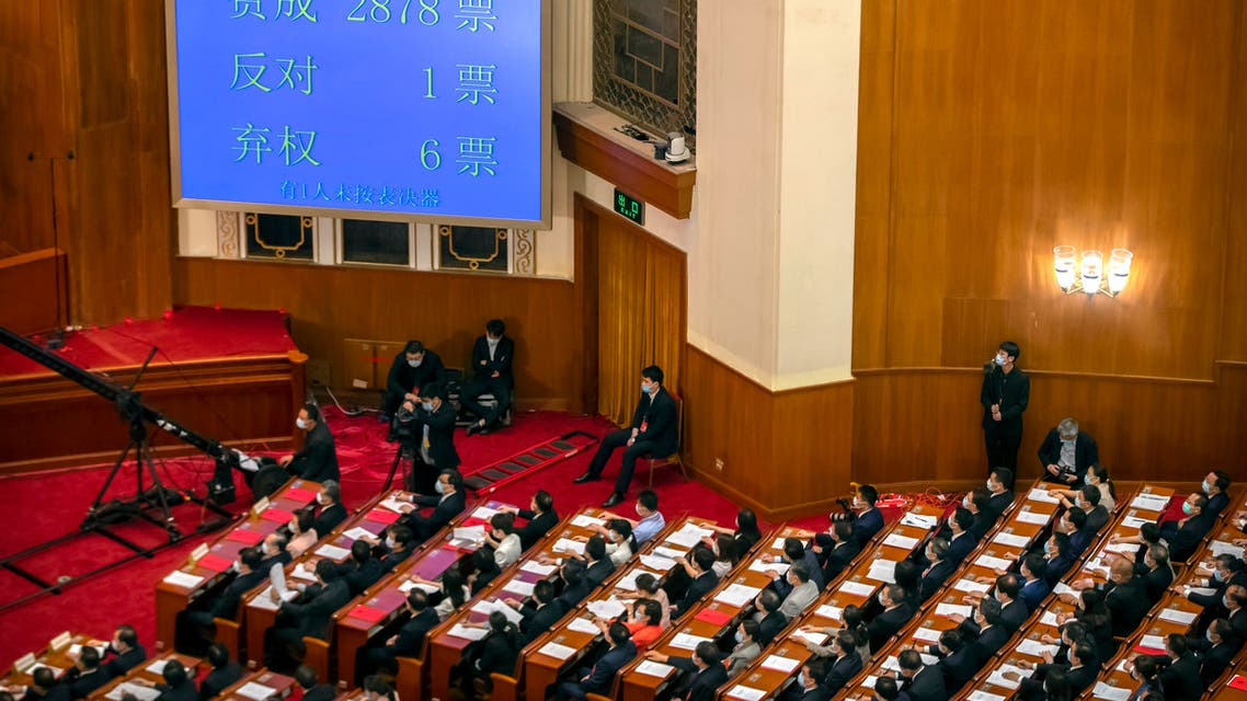 In this May 28, 2020, file photo, delegates applaud as a video screen shows the results of the vote on a piece of national security legislation concerning Hong Kong. (AP)