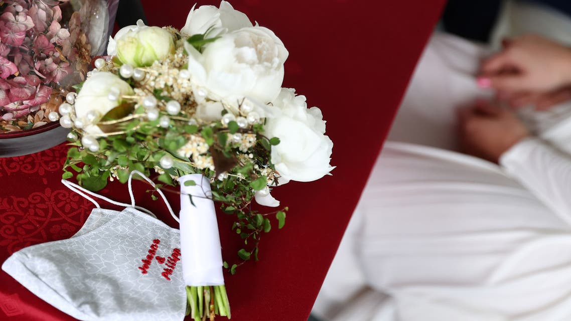 A protective face mask is seen next to the bride's flower bouquet during the wedding ceremony of Johanna and Philipp Sofsky at the temporary registry office in Hanau, Germany. (Reuters)