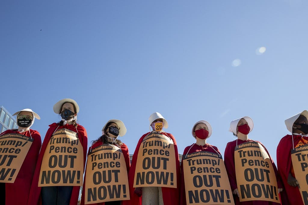 Dressed as handmaids, protesters attend the Women's March at Freedom Plaza on October 17, 2020 in Washington, DC. (AFP)