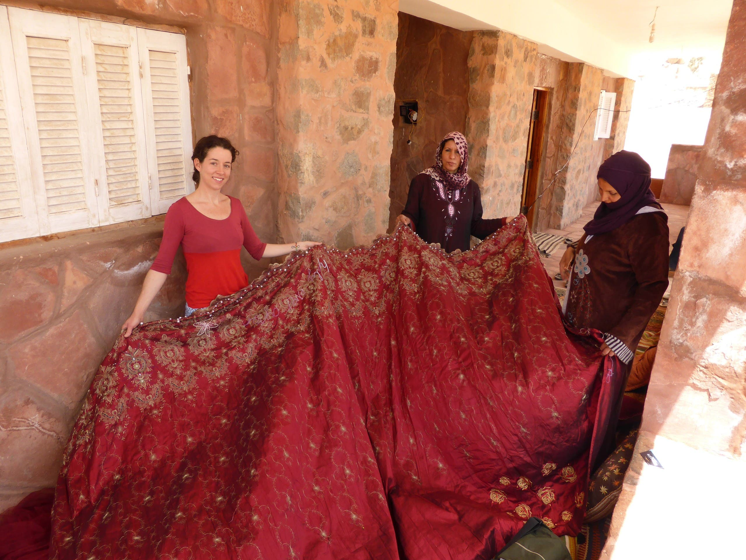 Kirstie Macleod (left) and Selema Gebaly (middle) looking at the material to be embroidered, in Saint Catherine, Sinai, Egypt. (Supplied: Kirstie Macleod)