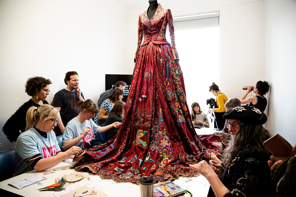 A group of women add small embroidery pieces to the hem at a pop-up exhibition in Bristol, UK, on International Women's Day. (Supplied: Mireya Gonzales)